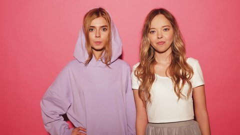 Two young funny smiling playful blond girls dressed in blue hoodie standing and isolated over pink background blowing bubblegum candy bubbles and chewing gum. Women looking at camera. 4k. Slow motion