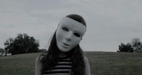 Young girl in white mask stands silently and creepily in a park