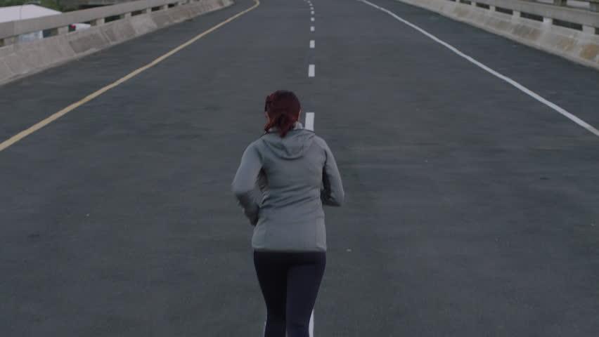 Woman runner jogging on city street exercising enjoying casual run at sunrise rear view   Shutterstock HD Video #1017906712