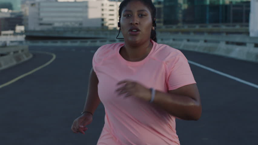 Overweight woman running exercising running weight loss challenge jogging in urban city at sunset wearing earphones | Shutterstock HD Video #1017906742