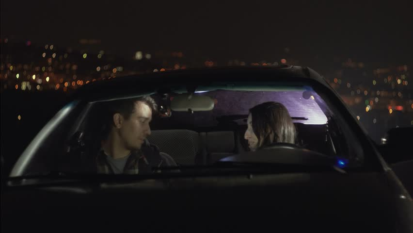 Young couple in love in car kissing on the background of night lights | Shutterstock HD Video #1017938062