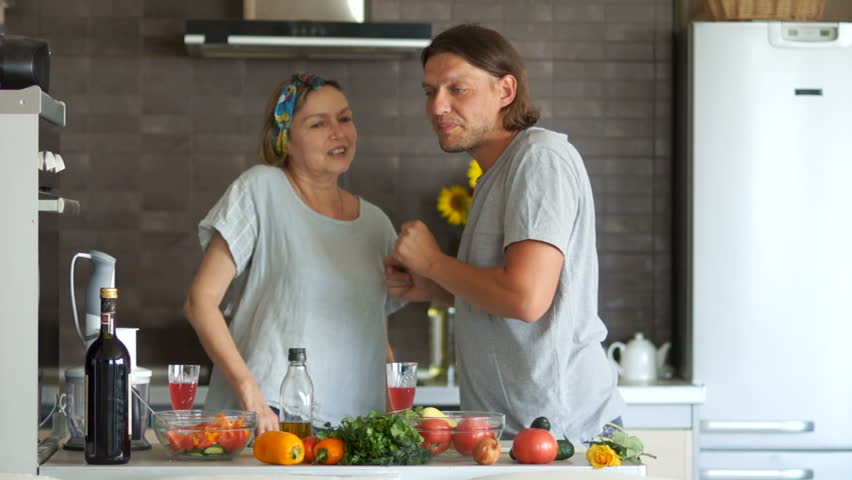 Mature woman and young man dancing and flirting in the kitchen. Couple with a difference in age. A man beckons a woman with his finger and playfully smiles