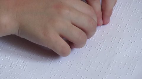Child learning Braille alphabet at school