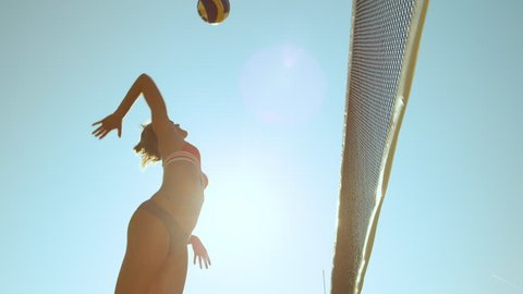 SLOW MOTION, LOW ANGLE, CLOSE UP, LENS FLARE: Athletic female beach volleyball player spikes the ball and scores a point during a competition. Cheerful girl enjoying the summer and playing voleyball.