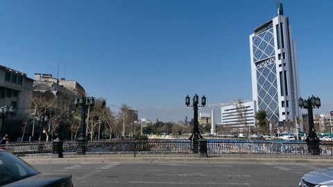 SANTIAGO, CHILE - Sep 11 2018. Moderate traffic and pedestrians crossing the Pio Nono bridge, with the view of the Telephone Tower, Andes mountains, Plaza Italia Obelisk and Mapocho river on the back.