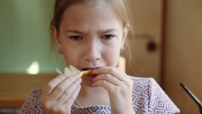 Beautiful young girl eats a lemon with a grimace on her face. | Shutterstock HD Video #1017989212