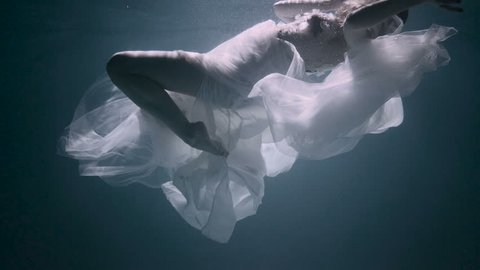 Young woman under the water, she is wearing a white dress.