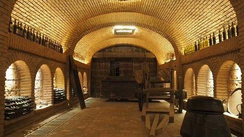 Large wine cellar interior.  High quality georgian red wine bottles. Wine making industry. Wines tasting shop. Storage for wine bottles and barrels
