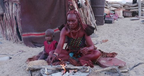4K side view of Himba woman in traditional dress with young child, filling a pipe and smoking outside their hut within their small compound, Namibia
