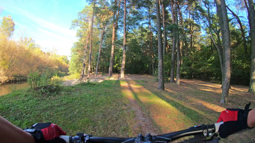 MTB cyclist riding a mountain bike on enduro trail near a river in autumn. Cross country mountain biking. Extreme speed cycling, first-person perspective view. Gimbal stabilized 4k | Shutterstock HD Video #1018033402