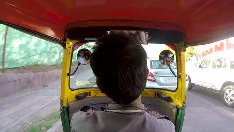 new delhi, Delhi / India - 06 24 2018: Footage of an auto rickshaw shot from the back seat running through traffic.