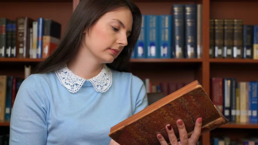 Footage pretty woman read book in library office. 4k education video | Shutterstock HD Video #1018086412