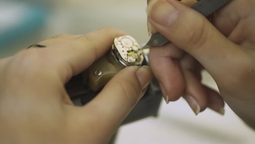 Production of watches, master configures the mechanism, view of the working mechanism of watches, gears and parts.