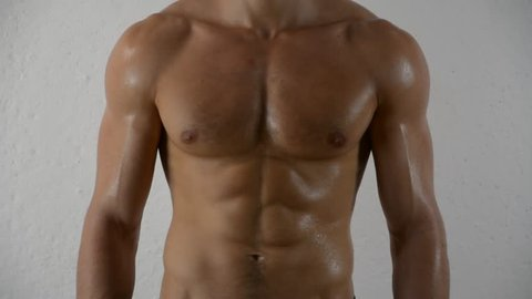 Close-up of torso of unrecognizable shirtless muscular man, standing, in studio shot against light grey background