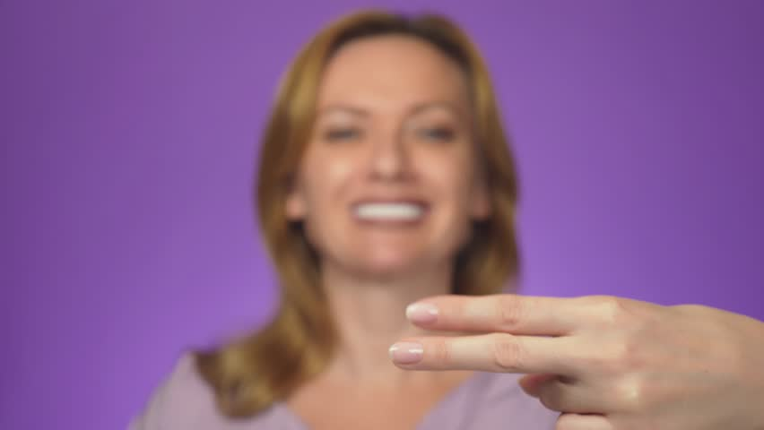 Young beautiful woman, blurred in the background, smiling. In the center of attention is her hand showing scissors symbol. background color | Shutterstock HD Video #1018115512