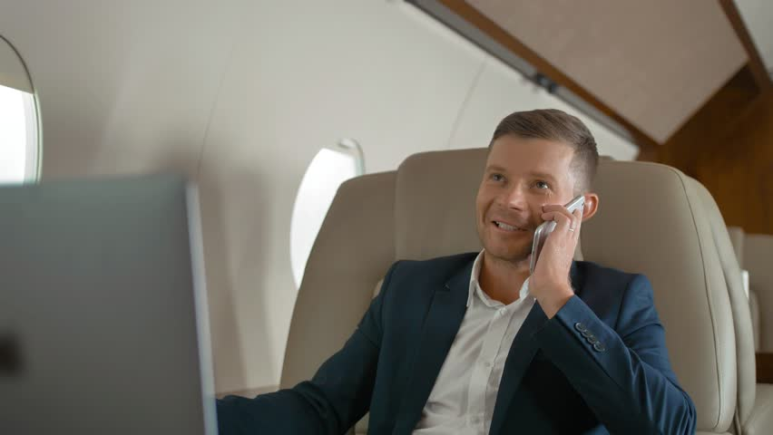 Close-up slow motion shot of rich mature businessman talk by phone partner connection aircraft jet travel. He work on laptop indoor of luxury expensive cabin. Happiness | Shutterstock HD Video #1018124212