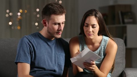 Sad couple reading bad news in a letter in the night at home