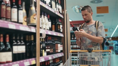 Grown man with backpack choosing bottle of wine on a shelf in a liquor store. Man buying alcohol, drinking wine red wine.