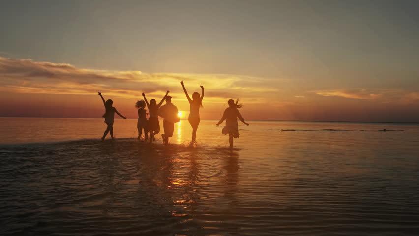 Big crowd of friends having fun at sunset sea beach. Beach vacations concept. Beauty and joyful teenager friends having fun, dancing, spraying over summer sunset. Beach party. Sun flare. Slow motion | Shutterstock HD Video #1018158532