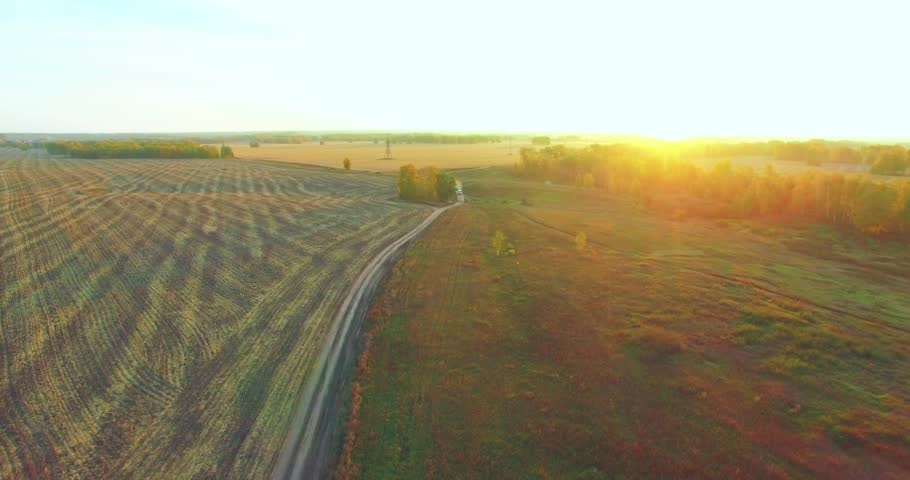 UHD 4K aerial view. Mid-air flight over rural dirt road with car. Yellow rural field at sunny autumn evening. Green trees on horizon. Horizontal movement. | Shutterstock HD Video #1018168252