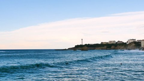 Landscape of the city of biarritz, next to the city's largest beach. There is the city lighthouse in the background. Filmed early in the evening. In the water, there are some surfers.
