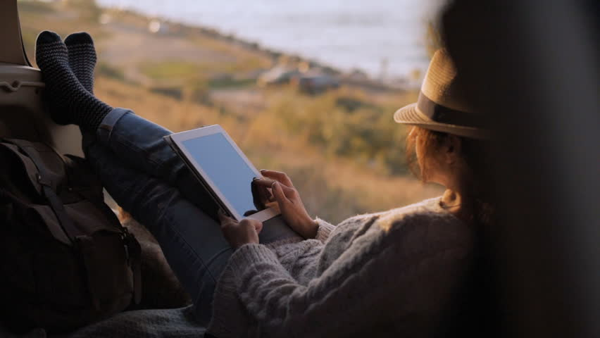 Woman traveler is holding touch pad, while is relaxing outdoors during his trip on the sea.  | Shutterstock HD Video #1018178752
