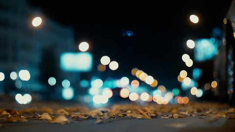 City lights and cars driving in traffic background. Autumn leaves scatter along the night road from the wind from passing cars. Out of focus background with blurry city lights and car light.