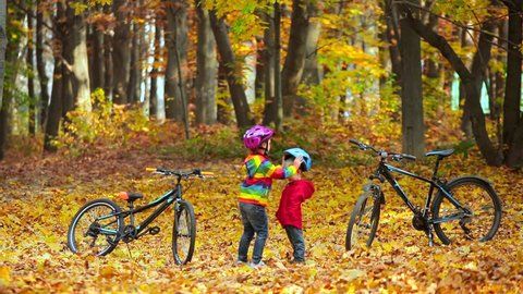 Little kids brother and sister in autumn Park. Older sister helping younger child to put his bike helmet. Active siblings with bicycles.