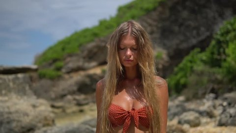 Beautiful saxy lady with blond hair and tatoos walks on the beach, dressed in red swimwear