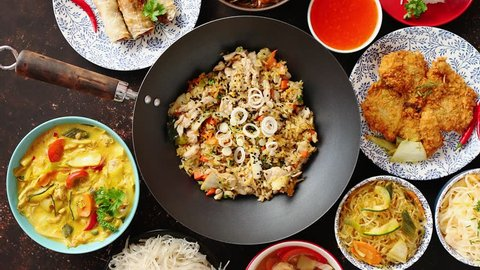 Asian oriental food composition in colorful dishware, served on dark rustic background, top view. Chinese, vietnamese, thai cuisine set. With copy space.