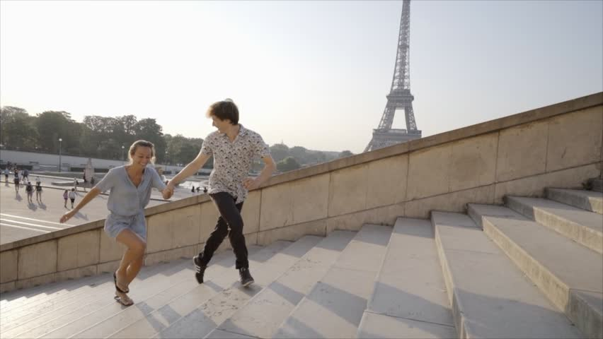 Young couple in Paris running up the stairs in front of the Eiffel Tower, France. Loving young people enjoying vacations and traveling in capital cities.  | Shutterstock HD Video #1018221352