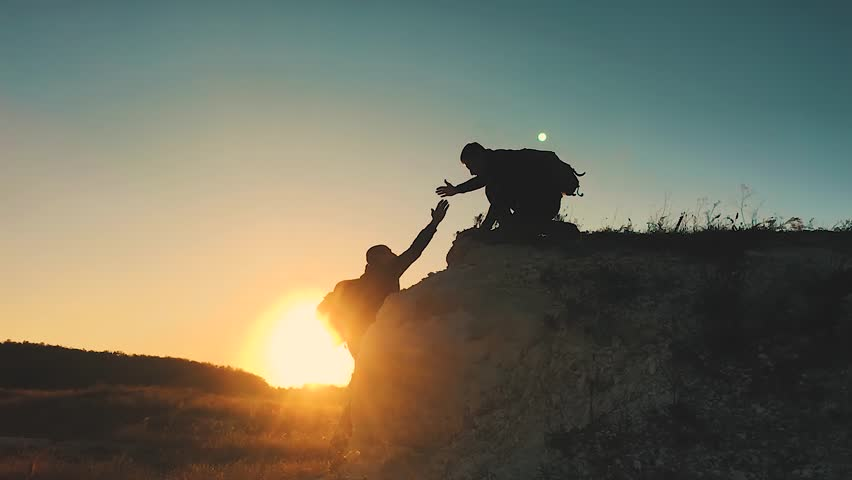 Silhouette of helping hand between two climber. two hikers on top of the mountain, a man helps a man to climb a sheer stone. couple hiking help each other silhouette in mountains with sunlight. | Shutterstock HD Video #1018229302