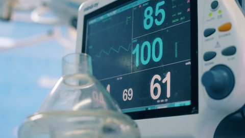 Close up of a hospital monitor with vital signs shown on it