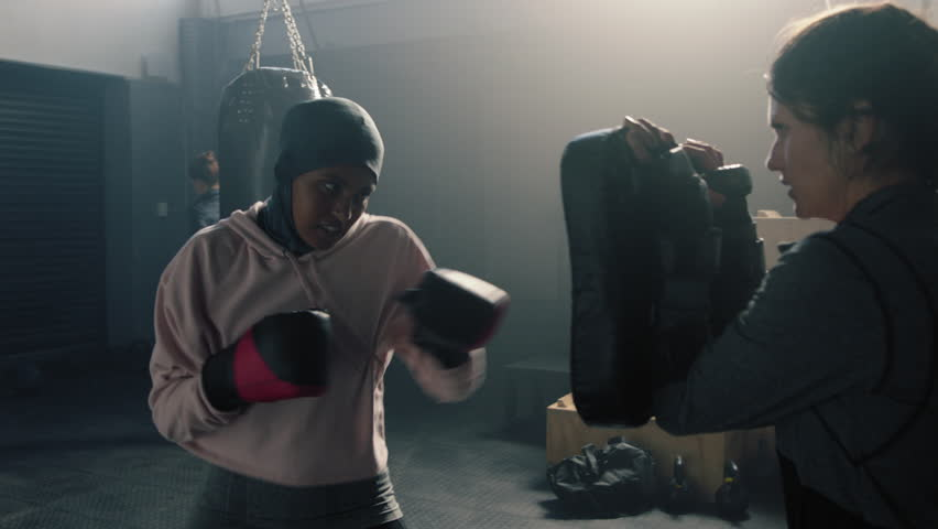 Muslim woman athlete training kickboxer coach teaching self defence friends enjoying intense exercise workout together in gym practice slow motion