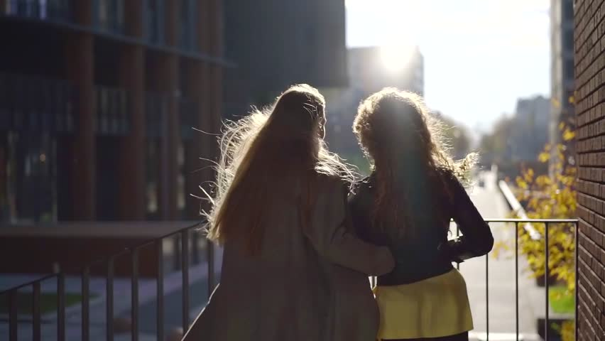 two charming young women are standing on city street in day in autumn, watching video by smartphone