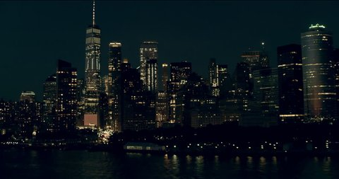 Aerial pan of downtown Manhattan skyscrapers and buildings, New York City, dark night light. Wide shot. 4k shot with a RED camera.