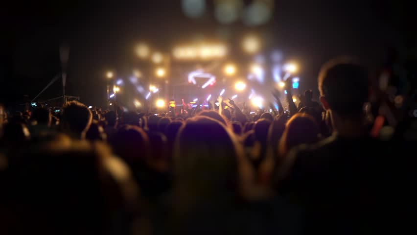 Happy people are watching an amazing musical concert. Merry fans jump and raise their hands up. Crowd of excited fans applauding to popular band performing favorite song. A group of fans with phones | Shutterstock HD Video #1018317022