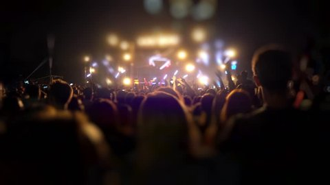 Happy people are watching an amazing musical concert. Merry fans jump and raise their hands up. Crowd of excited fans applauding to popular band performing favorite song. A group of fans with phones
