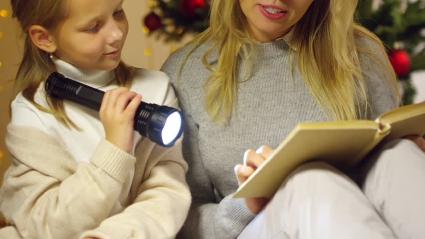 Tilt up of little girl holding flashlight and listening to mother while she reading fairytale in the living room on Christmas Eve | Shutterstock HD Video #1018338292