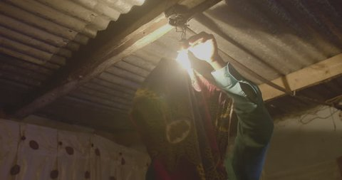 A man fixing his light bulb in his home in the township of Livingstone.