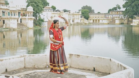 A wide shot of an elegant Indian classical dancer performing on a platform beside a beautiful lake in an old village. An attractive woman in traditional and colorful attire dancing in day outdoor