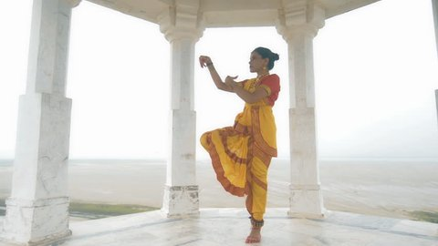 A wide shot of a confident Indian classical dancer dancing elegantly in white marble temple located on a hilltop. A moving shot of an attractive woman in traditional yellow sari performing folk dance