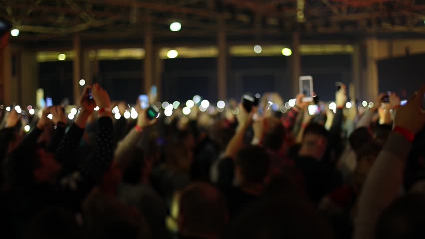 People waving hands with smartphones with flashlight. Live music concert. Slow motion, steadicam shot