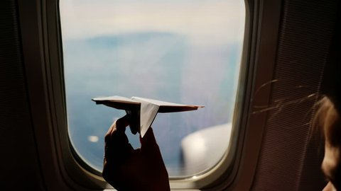 close-up. Silhouette of a child's hand with small paper plane against the background of airplane window. Child sitting by aircraft window and playing with little paper plane. during flight on airplane