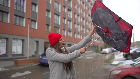 Young female sick woman, girl with umbrella standing. gust of wind pulls umbrella out of hand. girl holding umbrella. Bad miserable windy weather, high wind rain storm Flu cold disease health 4 K