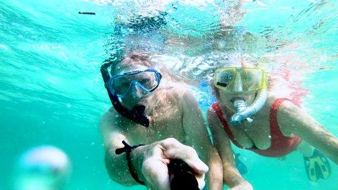 Selfie portrait of retired Caucasian American couple having fun snorkeling waving to camera making video diary underwater Bahamas USA