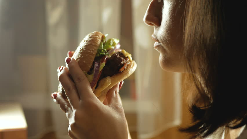 Young woman eating fast food, hamburger, close-up | Shutterstock HD Video #1018454752