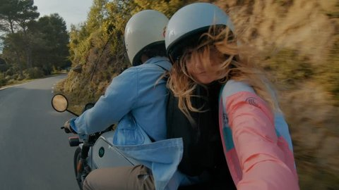 Young attractive couple of fashionable hipsters or millennials driving towards new exciting travel destination on motorbike on mountain forest road, wear white helmets, girl makes selfie.April 2018