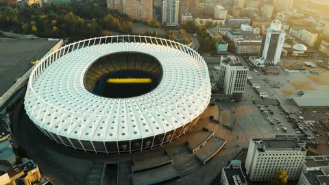 Aerial footage of the soccer stadium on the sunset in the big city. Big football arena in the evening. Empty stadium aerial footage.