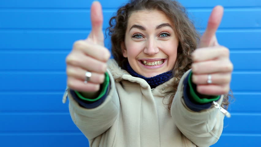 Happy young woman with curly hair and blue eyes shows thumb up or Like and smile in winter
